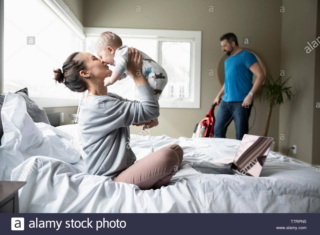 Tendre mère jouant avec son bébé sur le lit tandis que mari de vide en arrière-plan Photo Stock