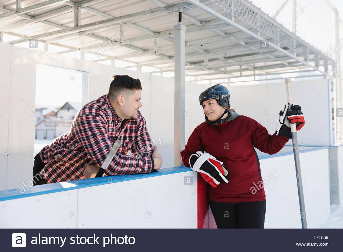 Couple playing hockey sur glace en plein air Photo Stock