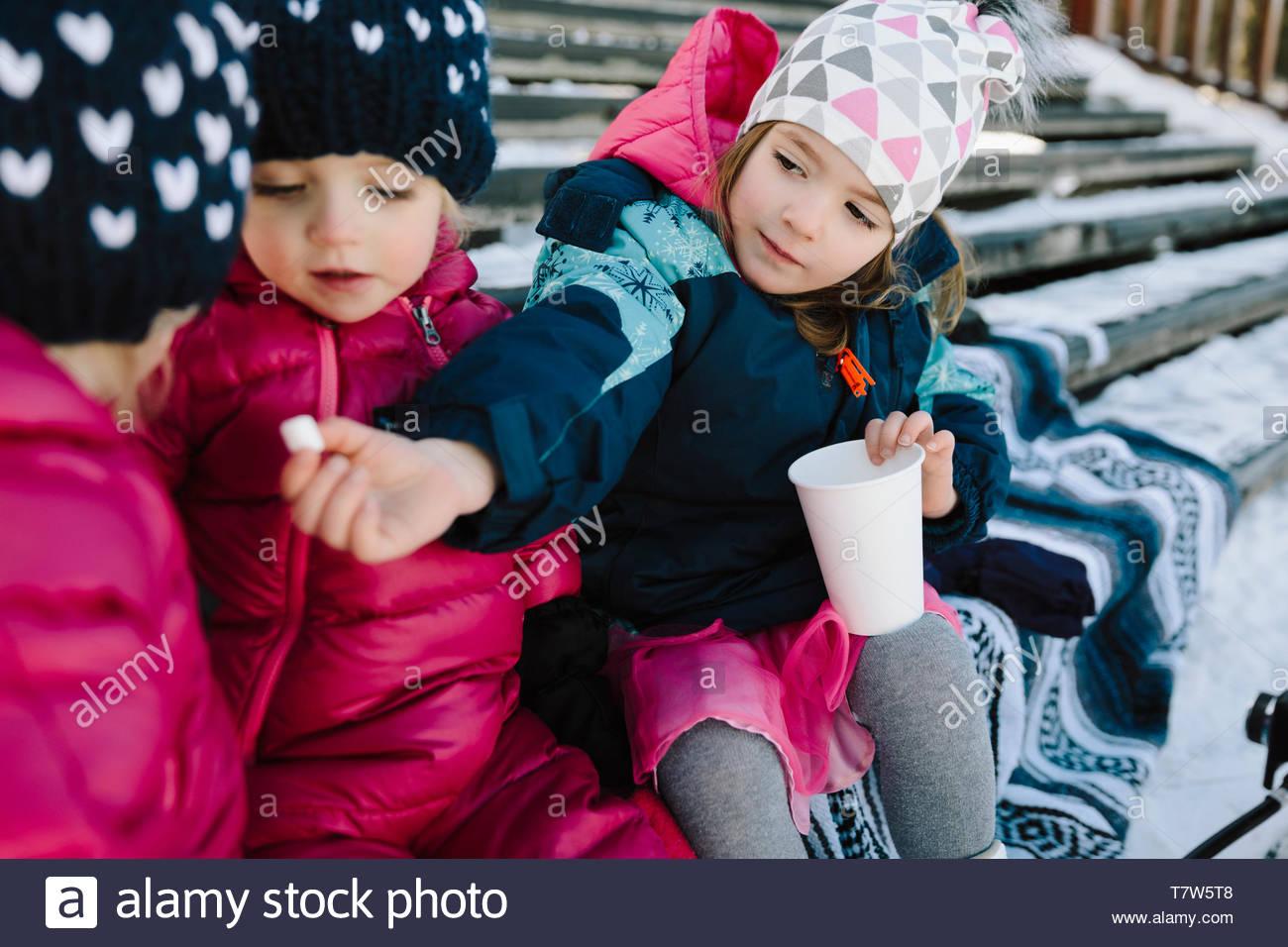 Cute toddler soeurs manger sur des mesures de neige Photo Stock