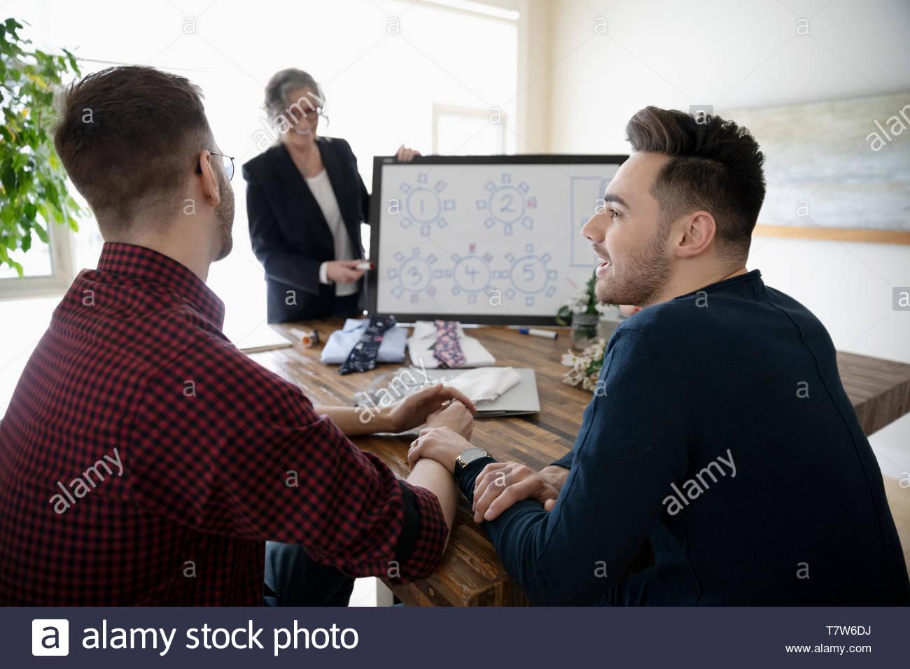 Homme couple gay affectueuse rencontre avec wedding planner, décider de l'attribution des sièges Photo Stock