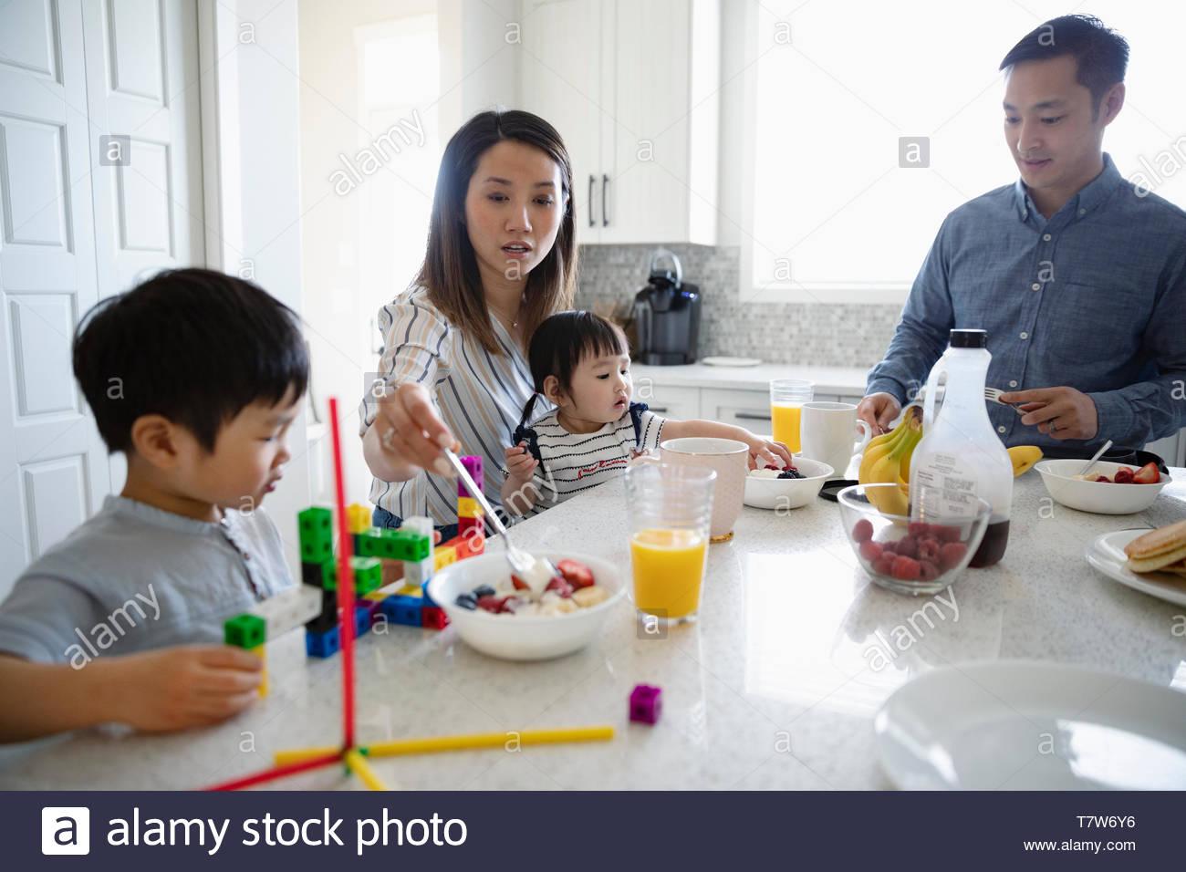 Le petit-déjeuner et repas de famille jouant avec des jouets dans la cuisine Banque D'Images