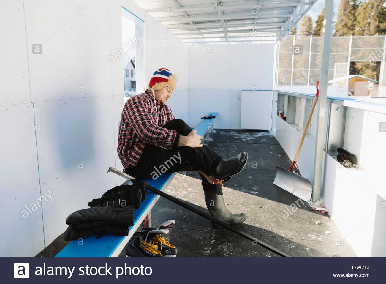 L'homme dépose les bottes, les prépare à jouer au hockey sur glace en plein air Photo Stock