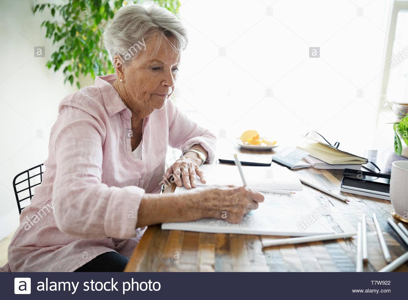 Femme senior dans un livre à colorier coloriage Photo Stock