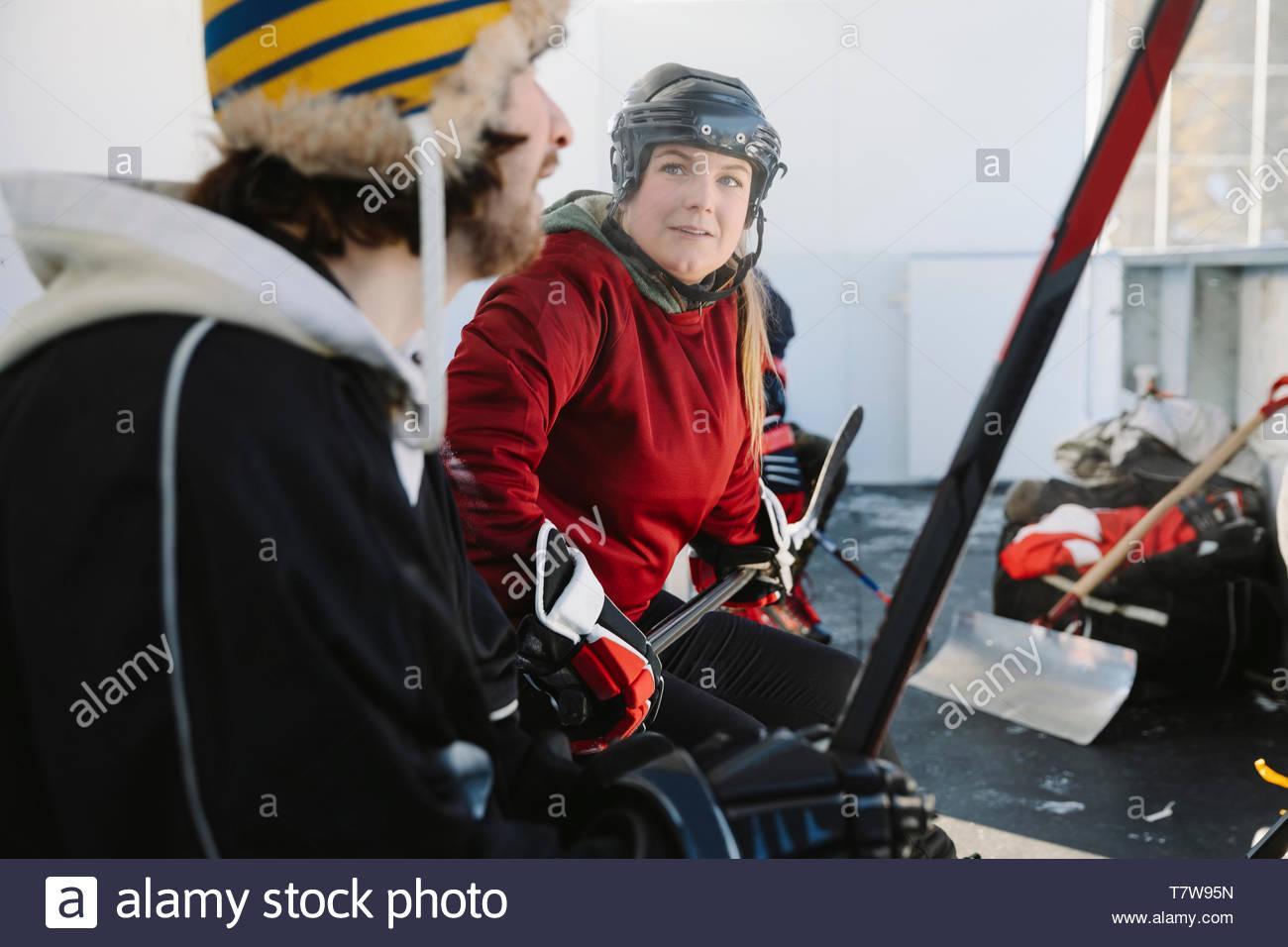 Les amis de jouer de hockey sur glace en plein air, assis sur le banc de touche Photo Stock