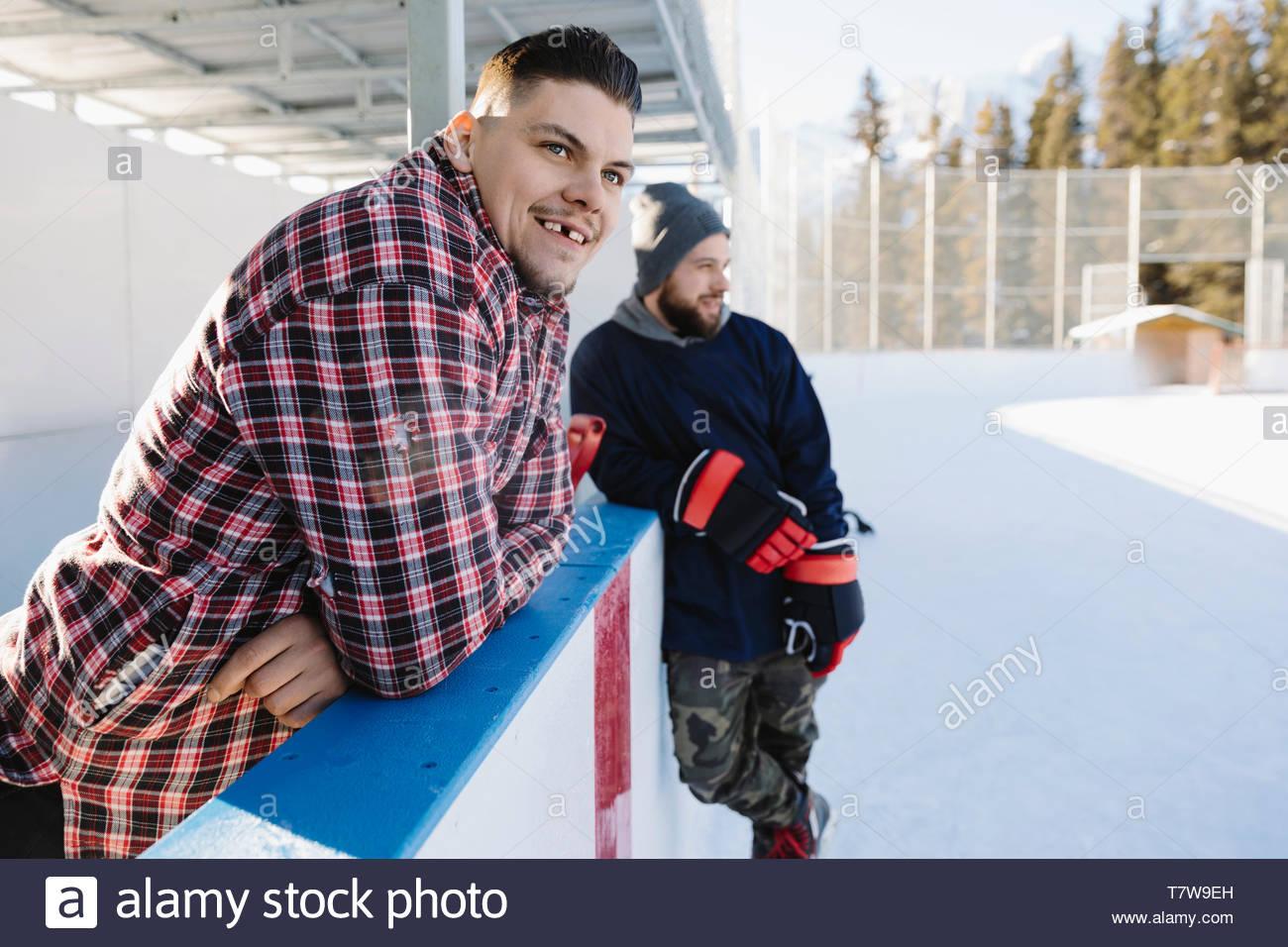 Smiling Men playing hockey sur glace en plein air Photo Stock