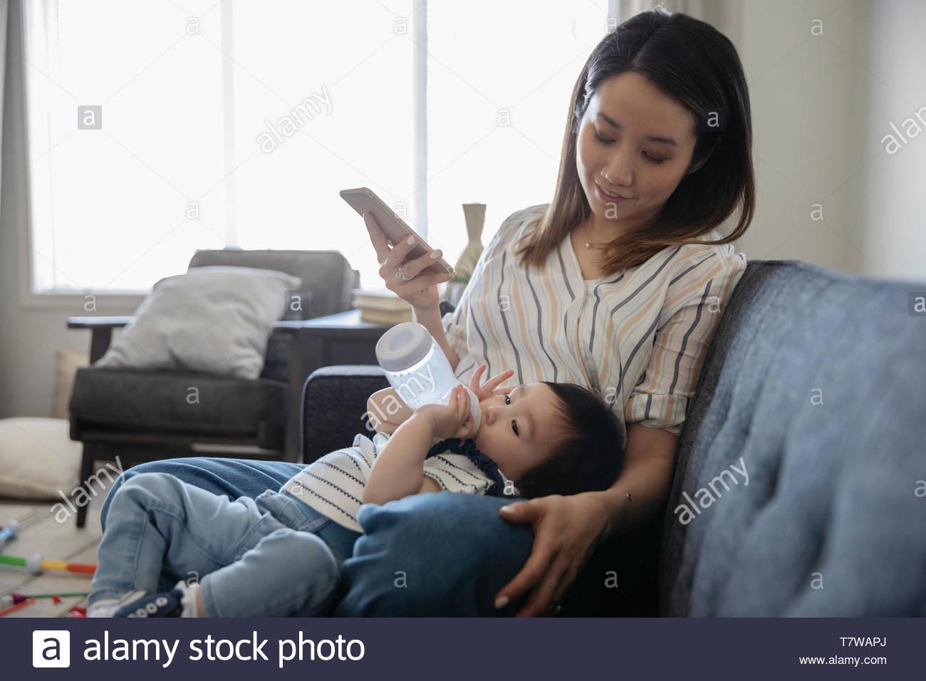 Mère regardant bébé fille avec bouteille de bébé Banque D'Images