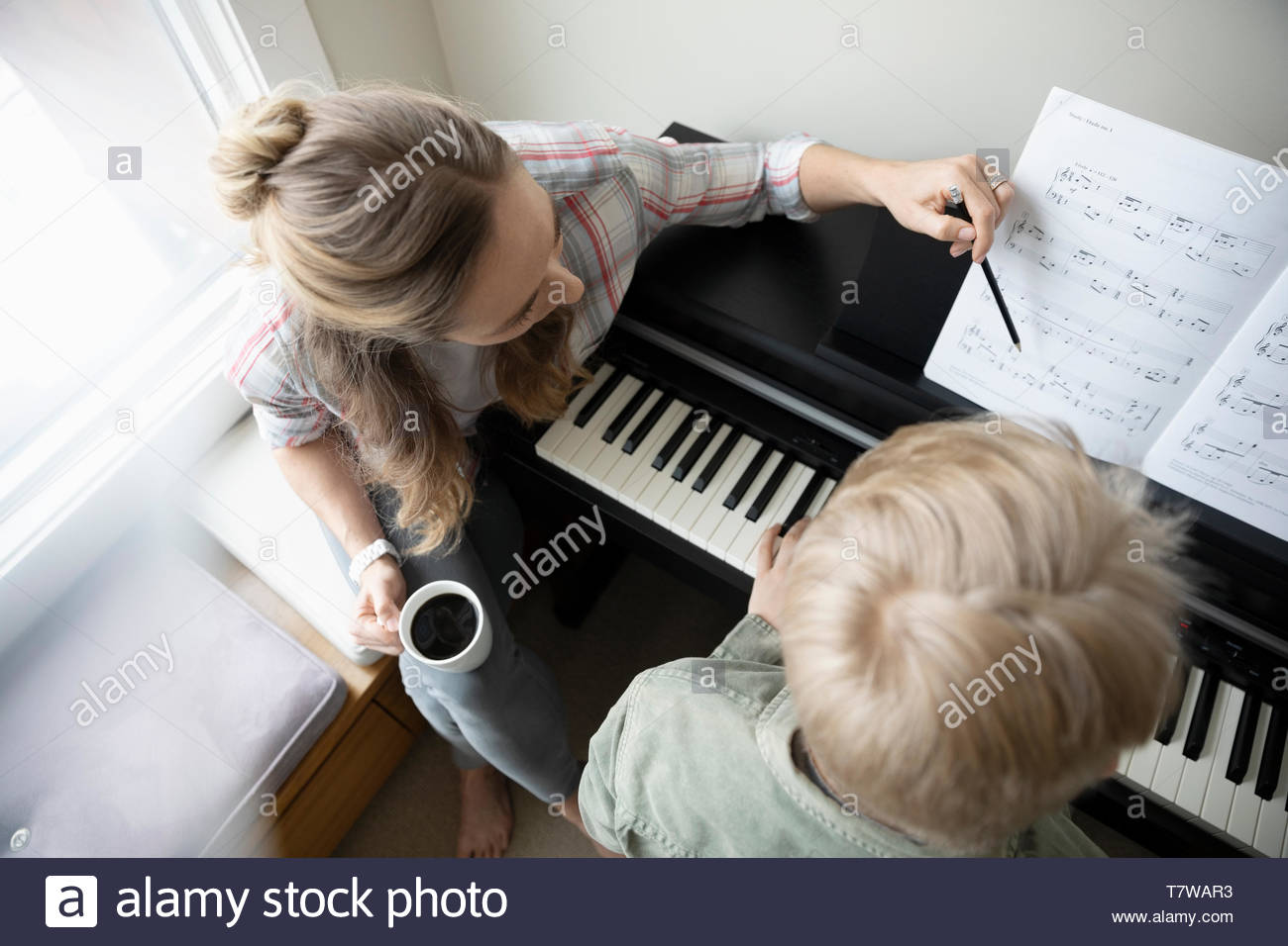 Mother helping son pratiquant à piano Photo Stock