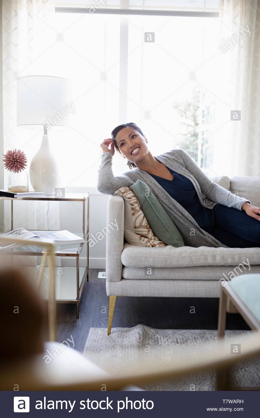 Happy woman relaxing on sofa du salon Photo Stock