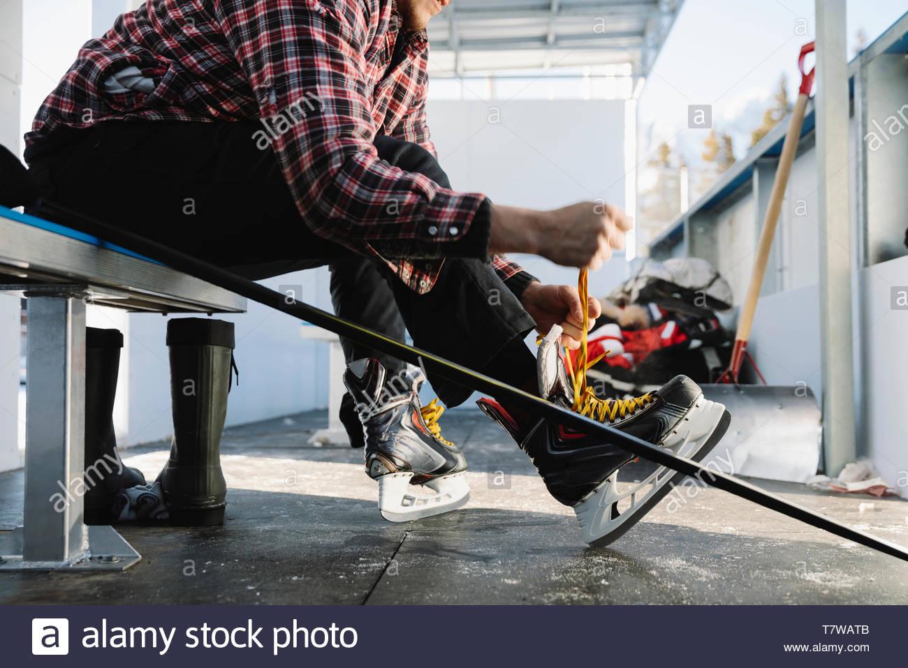 Homme attachant, de patins de hockey sur glace en plein air pour préparer Photo Stock