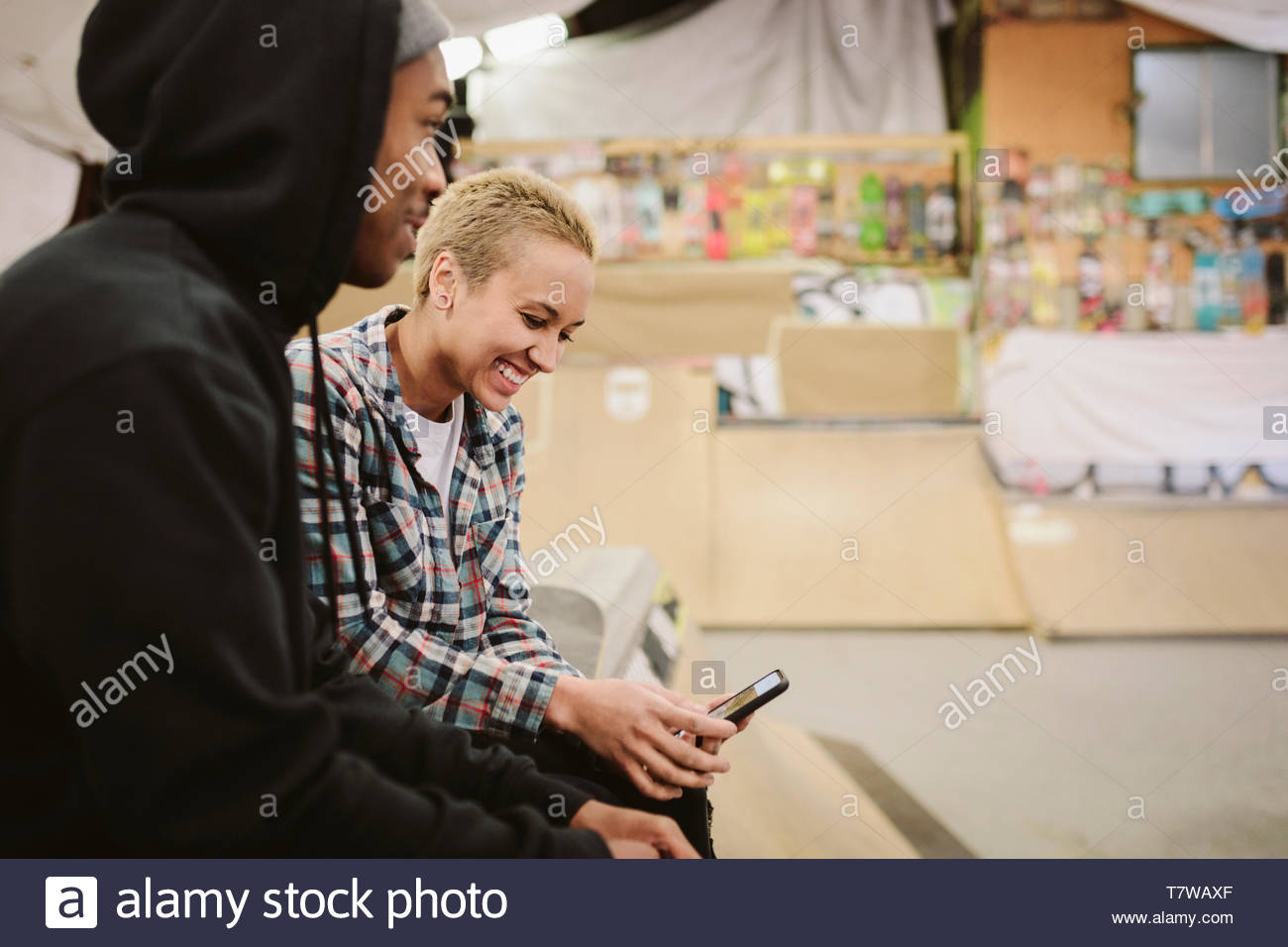 Young adult friends hanging out at indoor skate park Photo Stock