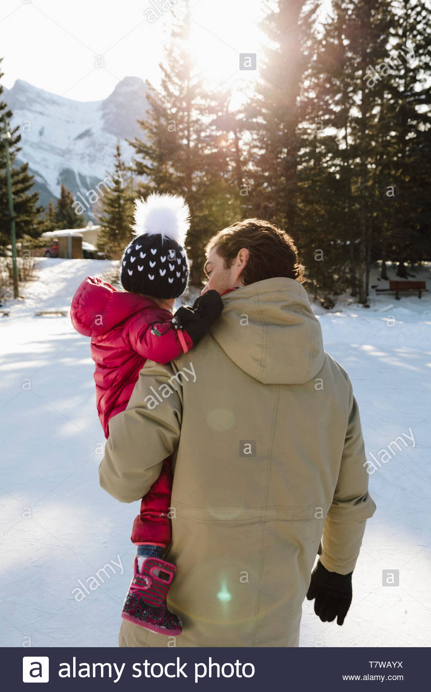 Father carrying toddler fille dans la neige Photo Stock