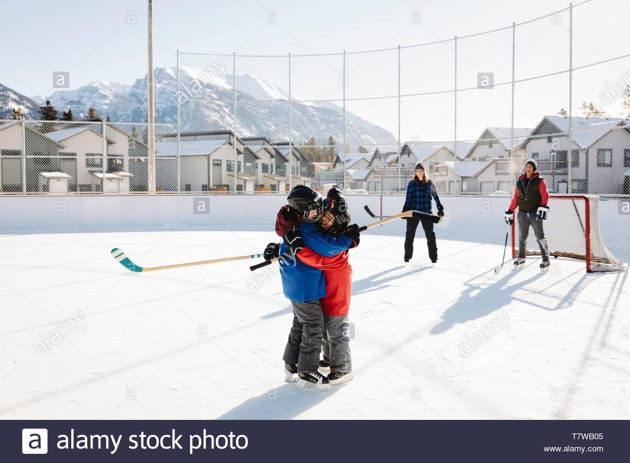 Jeu de hockey sur glace à l'extérieur de la famille, frères et sœurs hugging Banque D'Images
