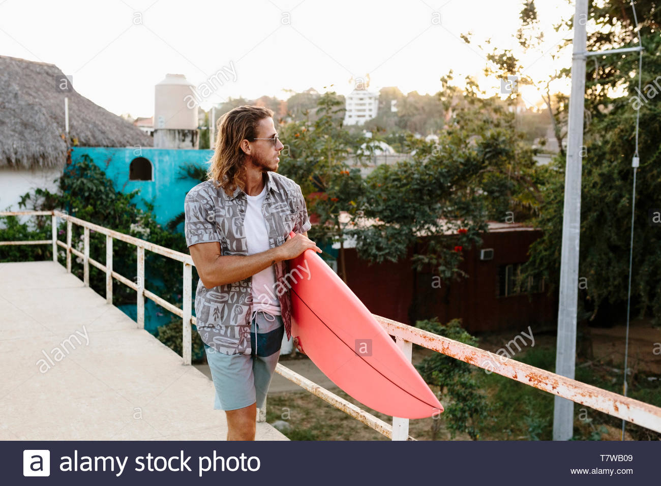 Young male surfer carrying surfboard, Mexique Photo Stock
