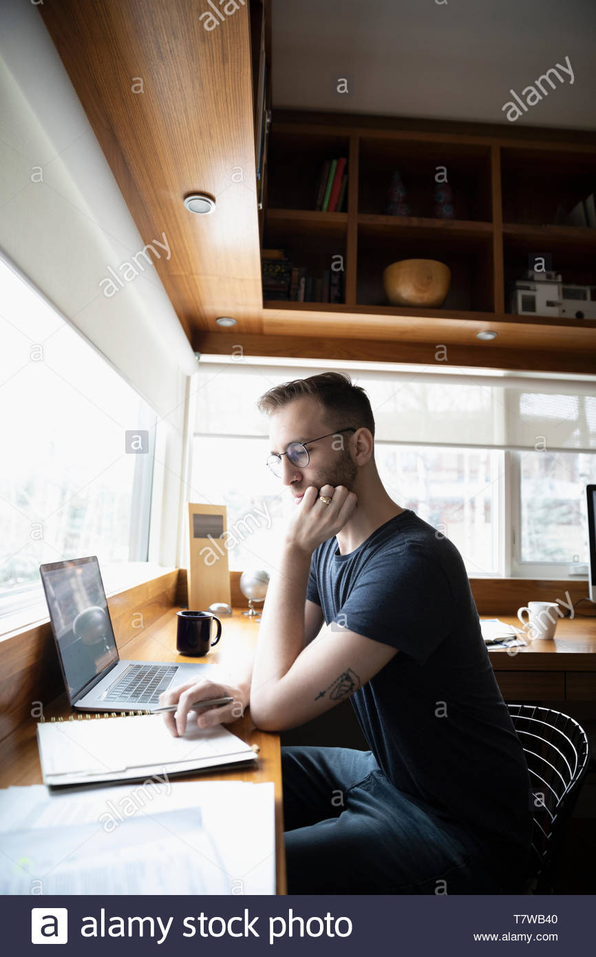 Focused man working from home, using laptop in office Photo Stock