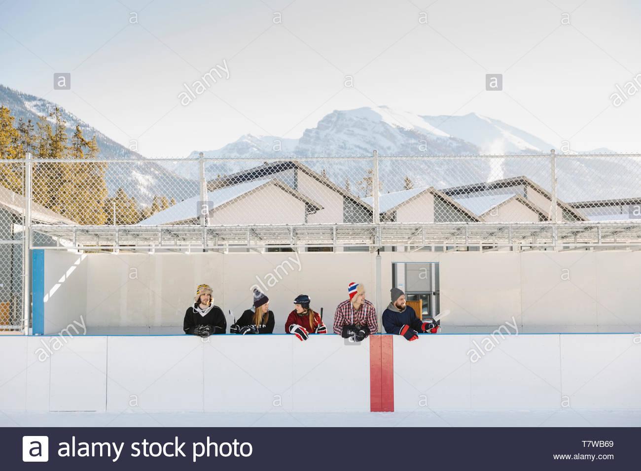 Les amis debout à côté de hockey sur glace en plein air montagne ci-dessous Photo Stock