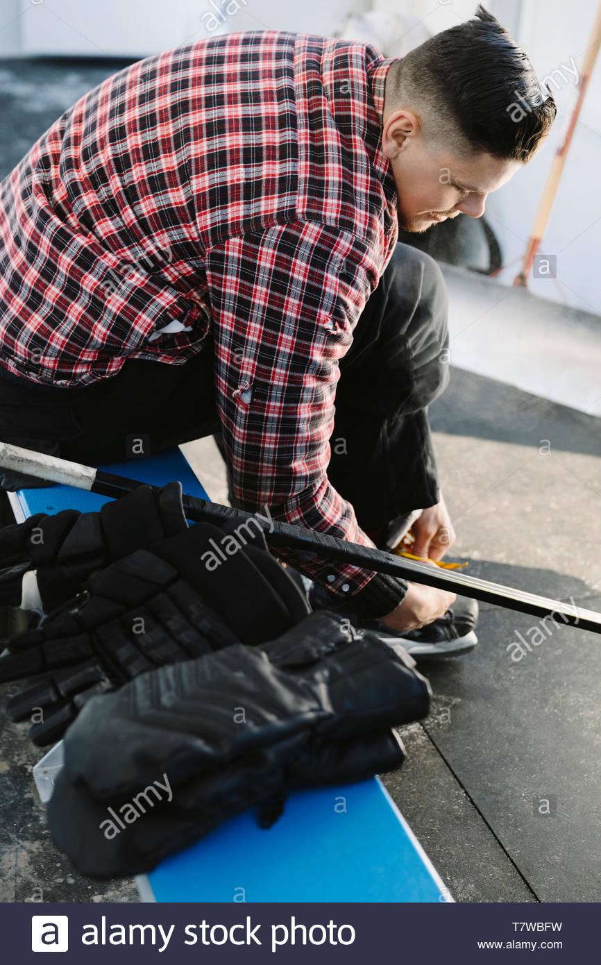 Homme attachant patin à glace, se préparant à jouer de hockey sur glace en plein air Photo Stock