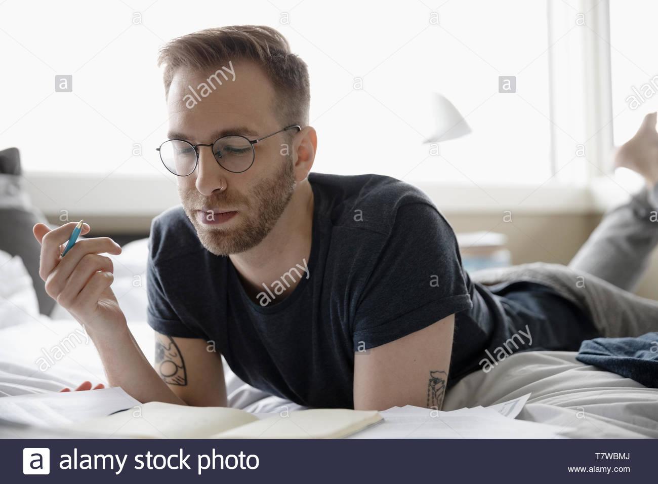 Homme travaillant à la maison, la lecture de documents on bed Photo Stock