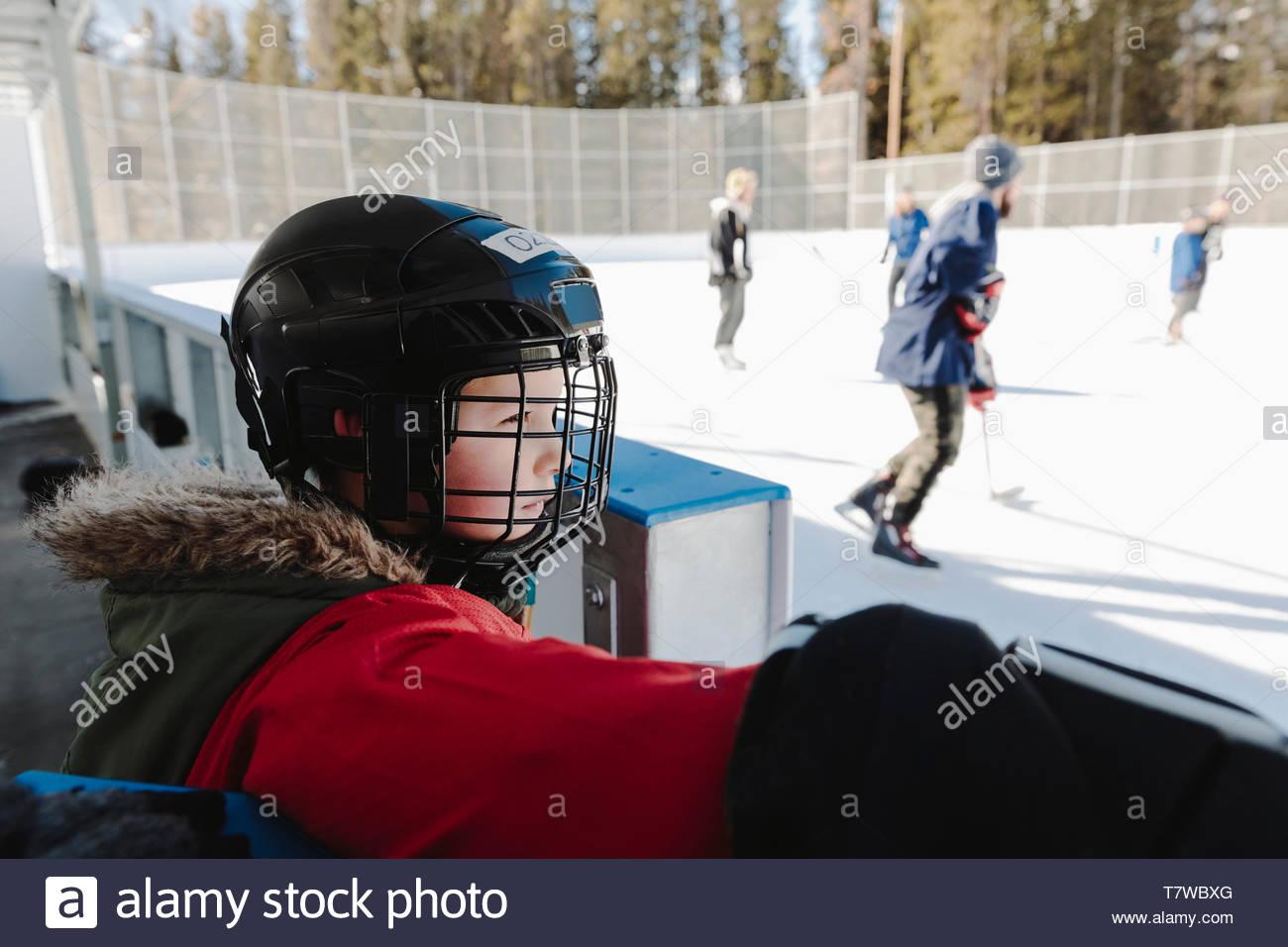 Garçon curieux de regarder le hockey sur glace en plein air à partir de la ligne de touche Photo Stock
