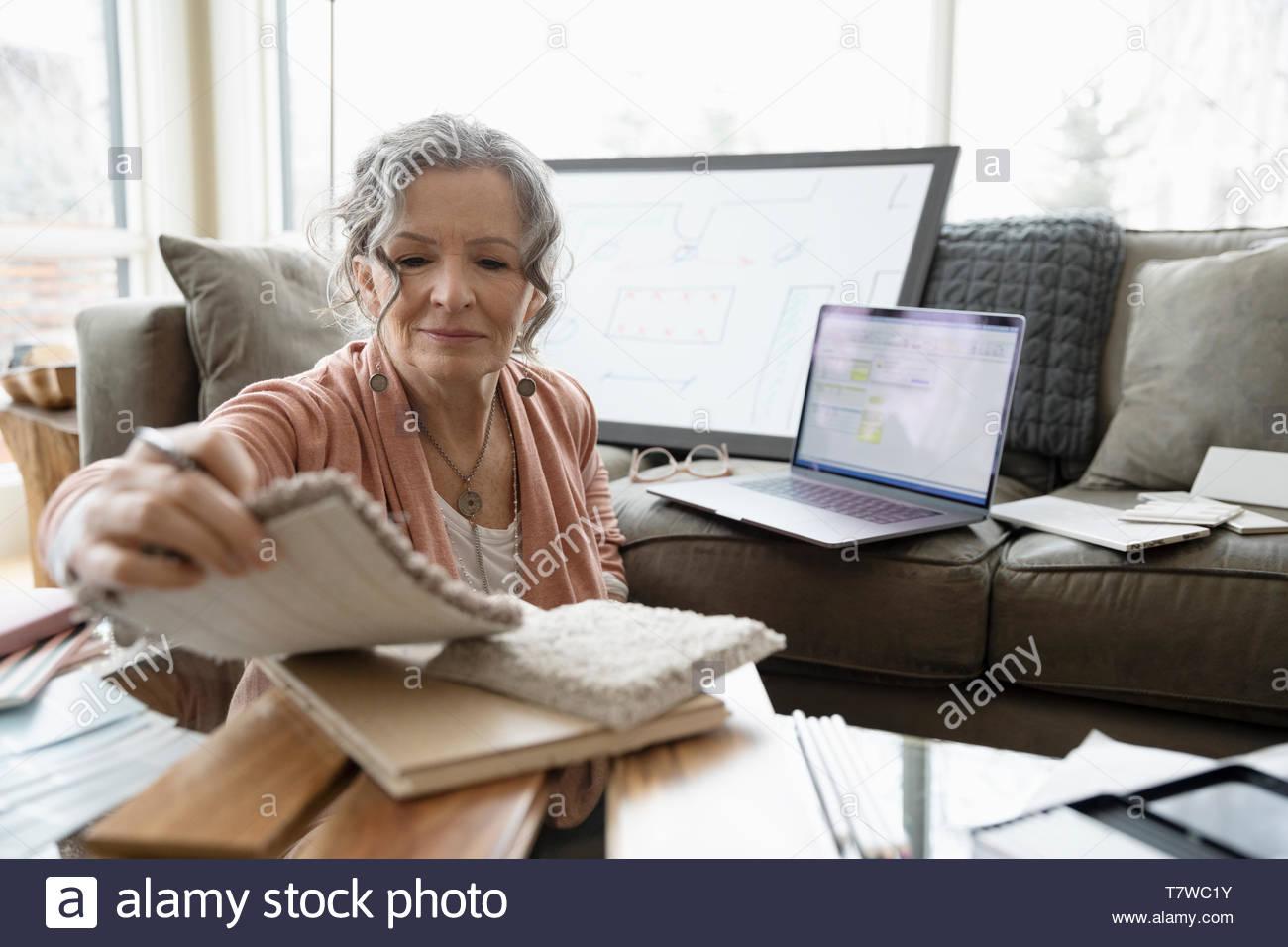 Femme Senior interior designer working from home, affichage des nuanciers dans salle de séjour Photo Stock