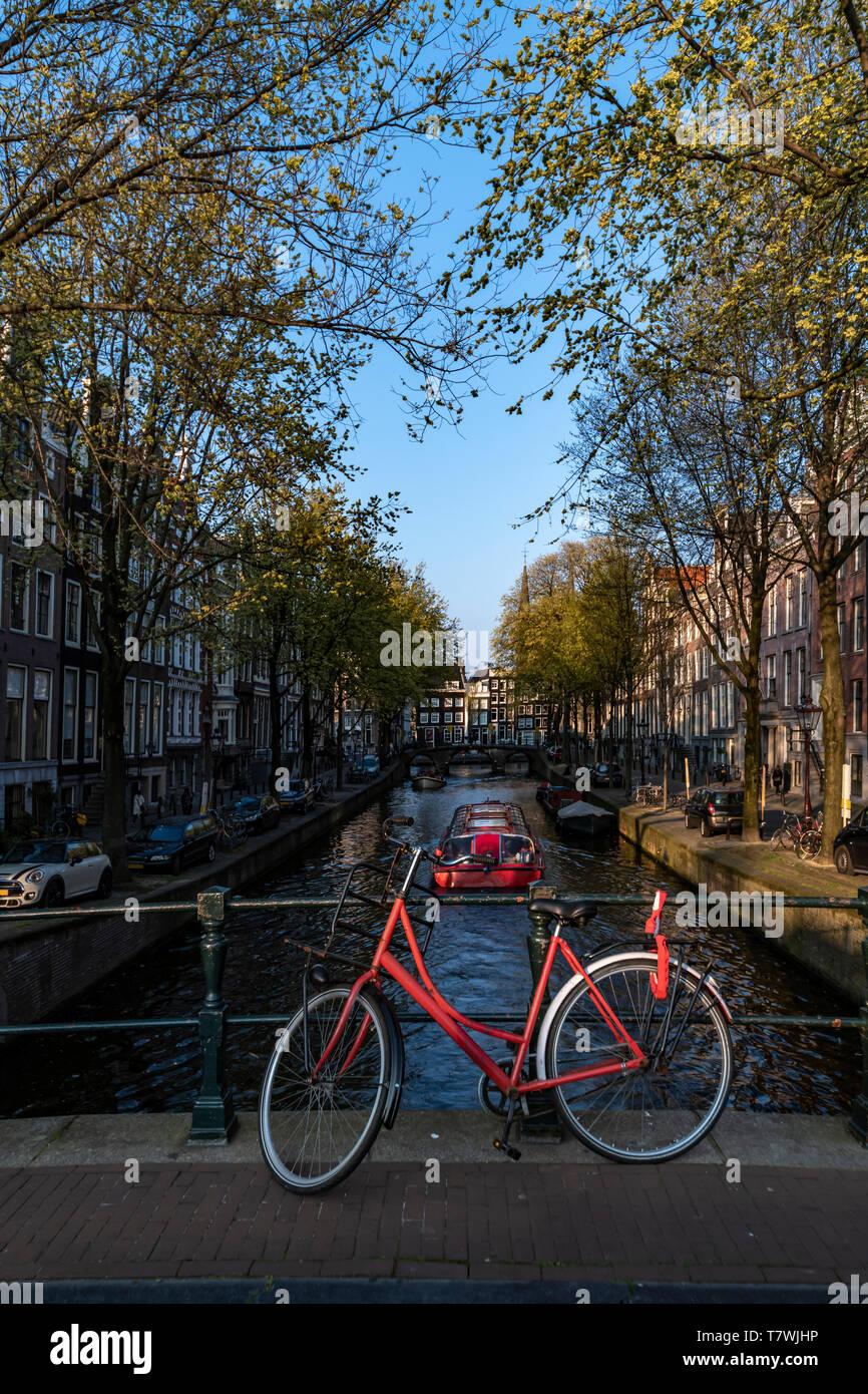 Parking vélo rouge sur le pont sur l'eau calme d'un canal avec un bateau donnant un aller-retour pour les touristes, Amsterdam, Pays-Bas Banque D'Images