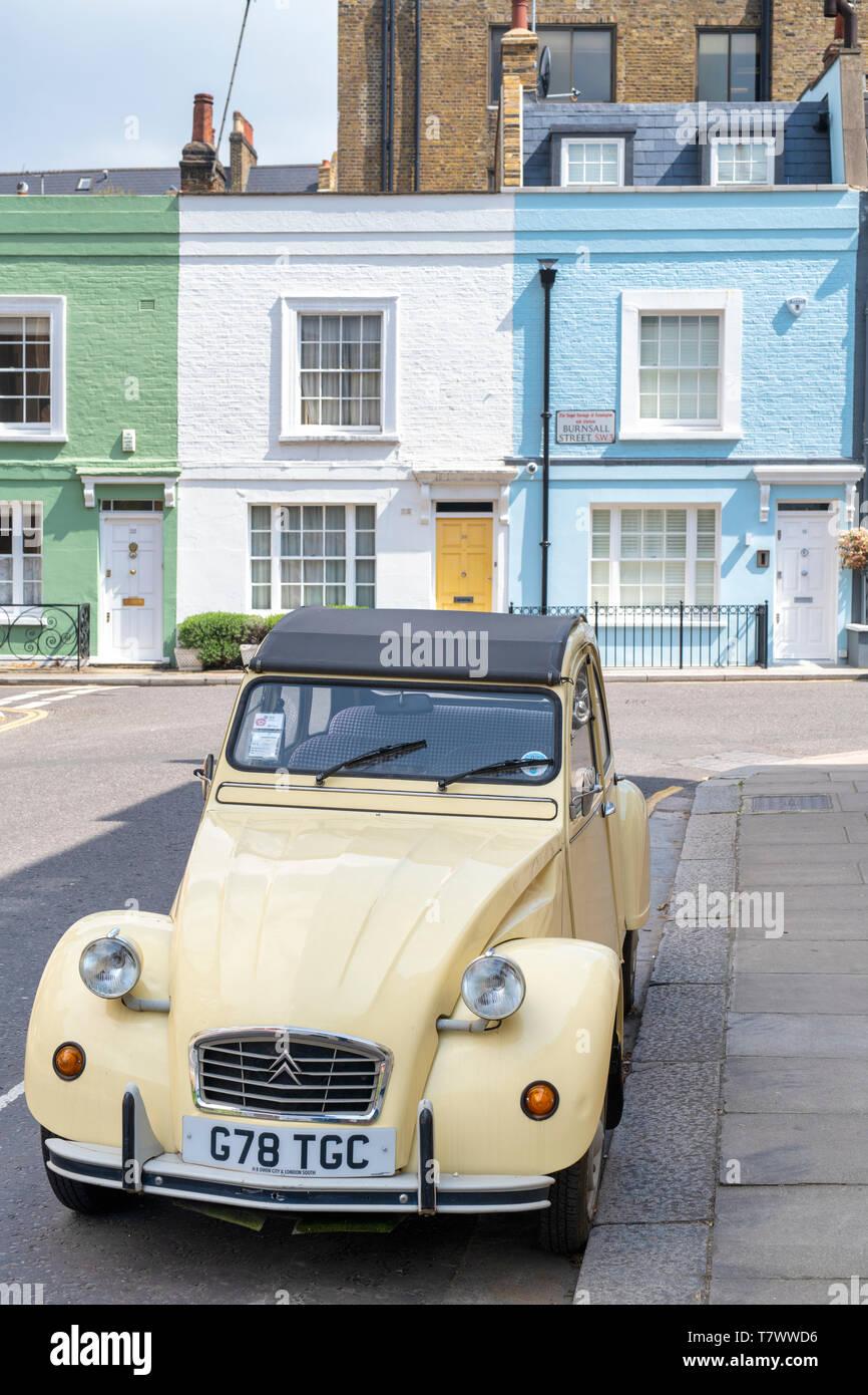 Citroën 2 CV voiture en face de maisons peintes en couleurs dans Burnsll street , Chelsea, Londres, Angleterre Photo Stock