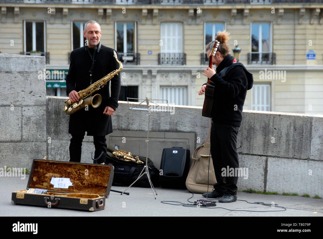 Deux des musiciens ambulants dans la rue à Paris, France, avec une variété d'instruments et la vente des CD Photo Stock