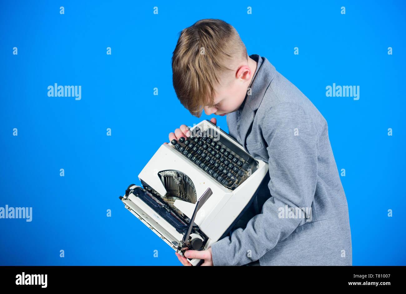 Retro et vintage. Vente-débarras. Étude rétrospective. Garçon tenir la machine à écrire rétro sur fond bleu. Que faire avec cette chose. Plus d'actualité. J'ai besoin de gadgets modernes au lieu cette rétro. Gadget désuet. Photo Stock