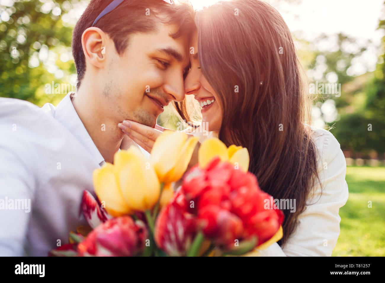 Happy young couple in love hugging avec bouquet de fleurs du printemps à l'extérieur. Homme doué sa petite amie avec des tulipes Banque D'Images