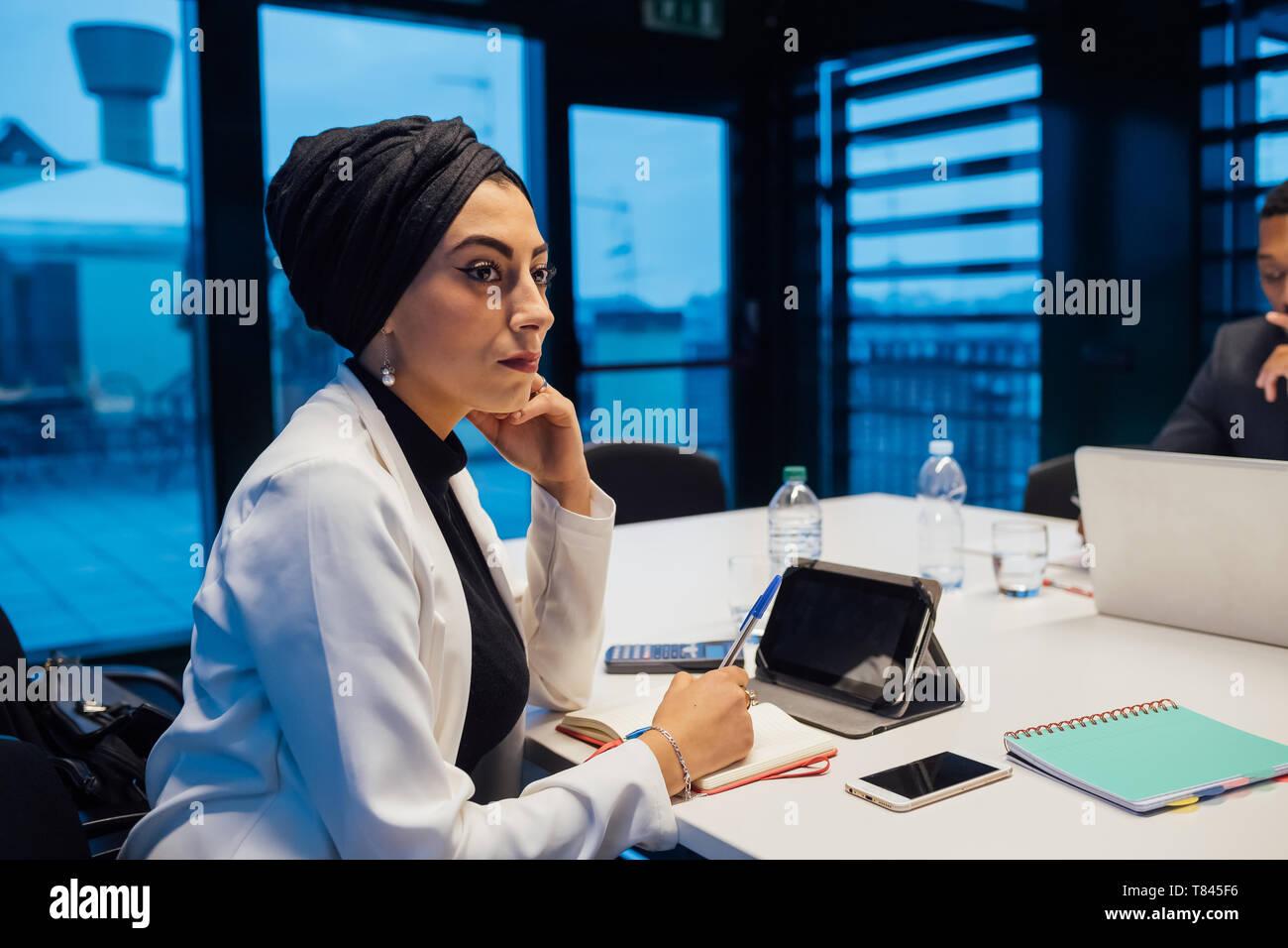 Businesswoman listening au cours de réunion de la table de conférence Banque D'Images