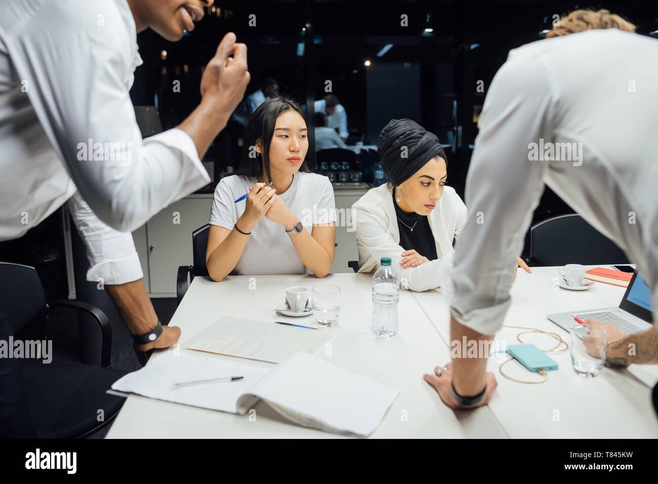 Les hommes et les femmes d'avoir discuté de la réunion de la table de conférence Banque D'Images