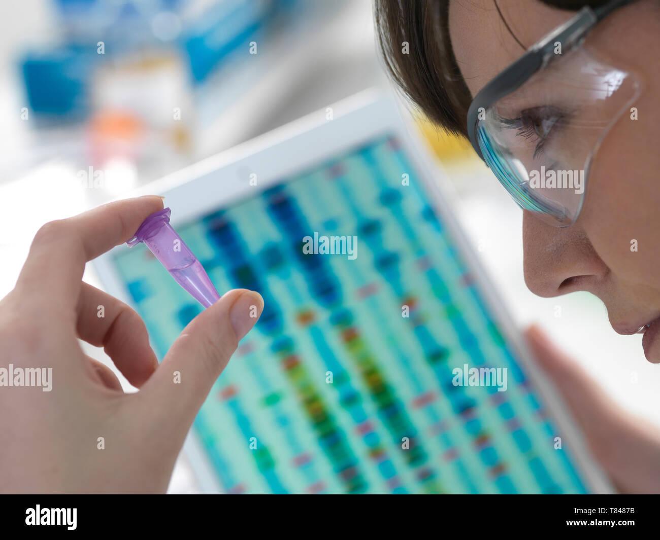 L'examen scientifique des femmes dans l'échantillon d'ADN avec tube Eppendorf résultats sur digital tablet in laboratory Banque D'Images
