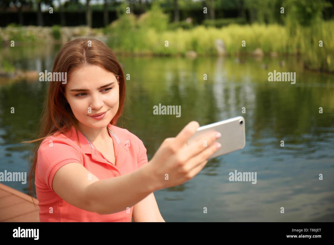 Jeune femme en tenant près de river selfies Banque D'Images