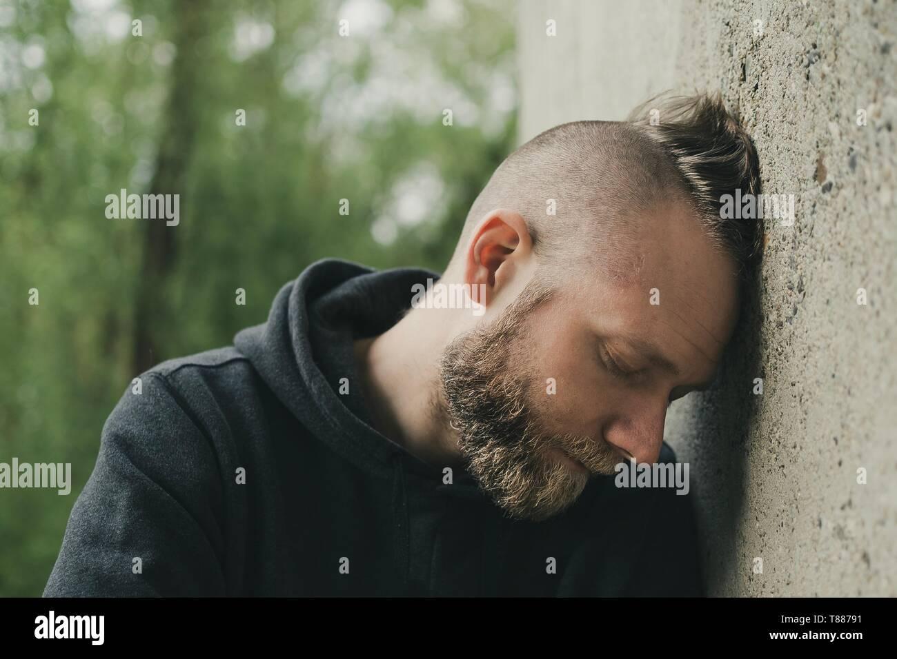 Déprimé et homme seul sa tête contre un mur Banque D'Images