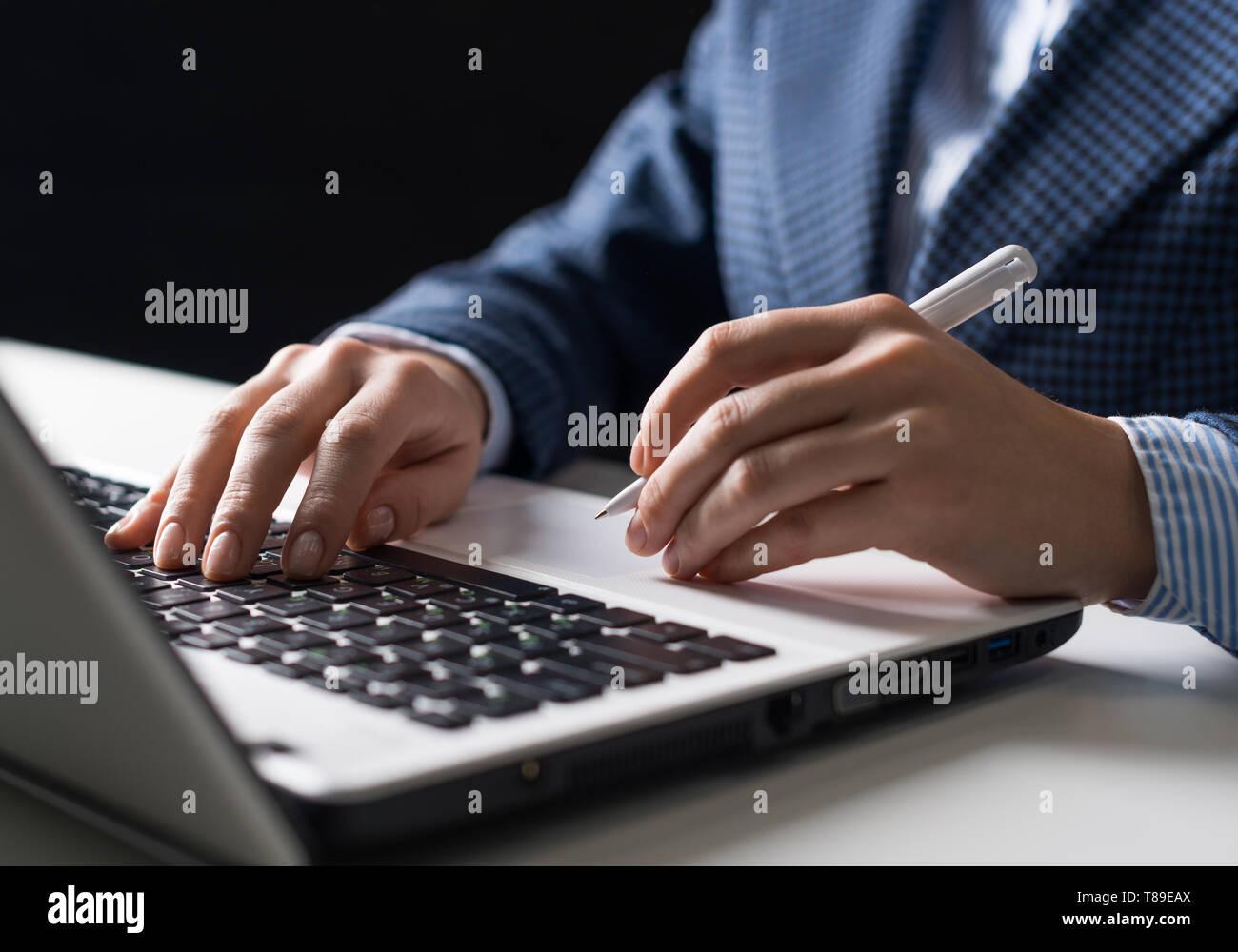 L'homme en costume sitting at desk with laptop Banque D'Images