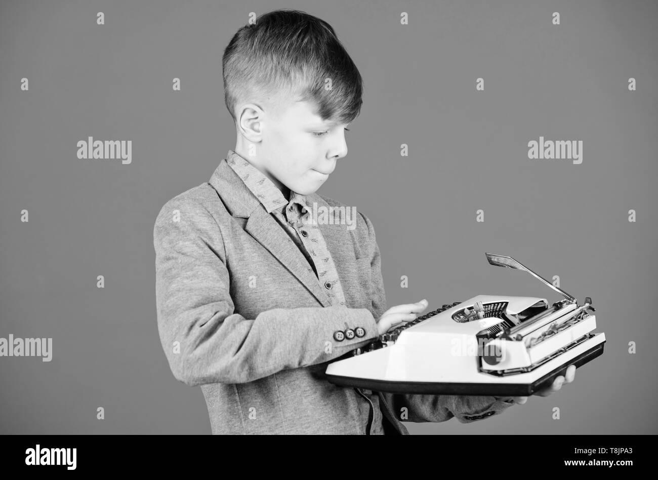 Plus d'actualité. J'ai besoin de gadgets modernes au lieu cette rétro. Gadget désuet. Retro et vintage. Vente-débarras. Étude rétrospective. Garçon tenir la machine à écrire rétro sur fond bleu. Que faire avec cette chose. Photo Stock