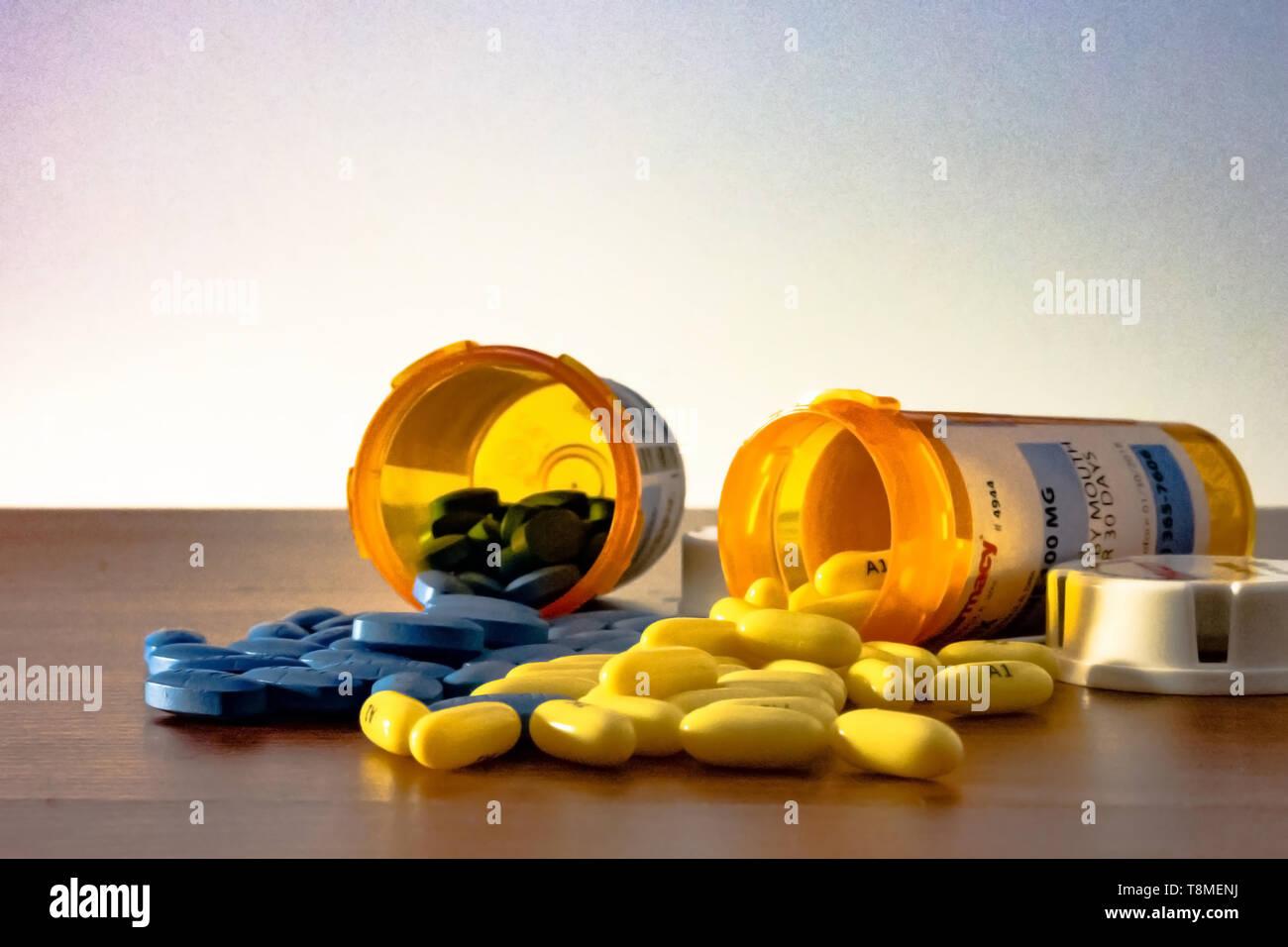 Deux bouteilles d'ordonnance annulée avec le bleu et le jaune pills spilling out sur la table avec un fond blanc, représentant de l'épidémie en Amérique p Banque D'Images
