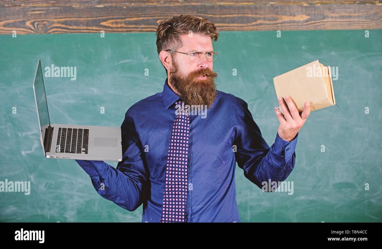 Hipster barbu de l'enseignant est titulaire d'adresses et ordinateur portable. Choisissez la méthode d'enseignement droit. Le choix d'enseignants de l'enseignement moderne approche. Avantages des technologies modernes. Au lieu moderne obsolètes. Papier contre numérique. Photo Stock