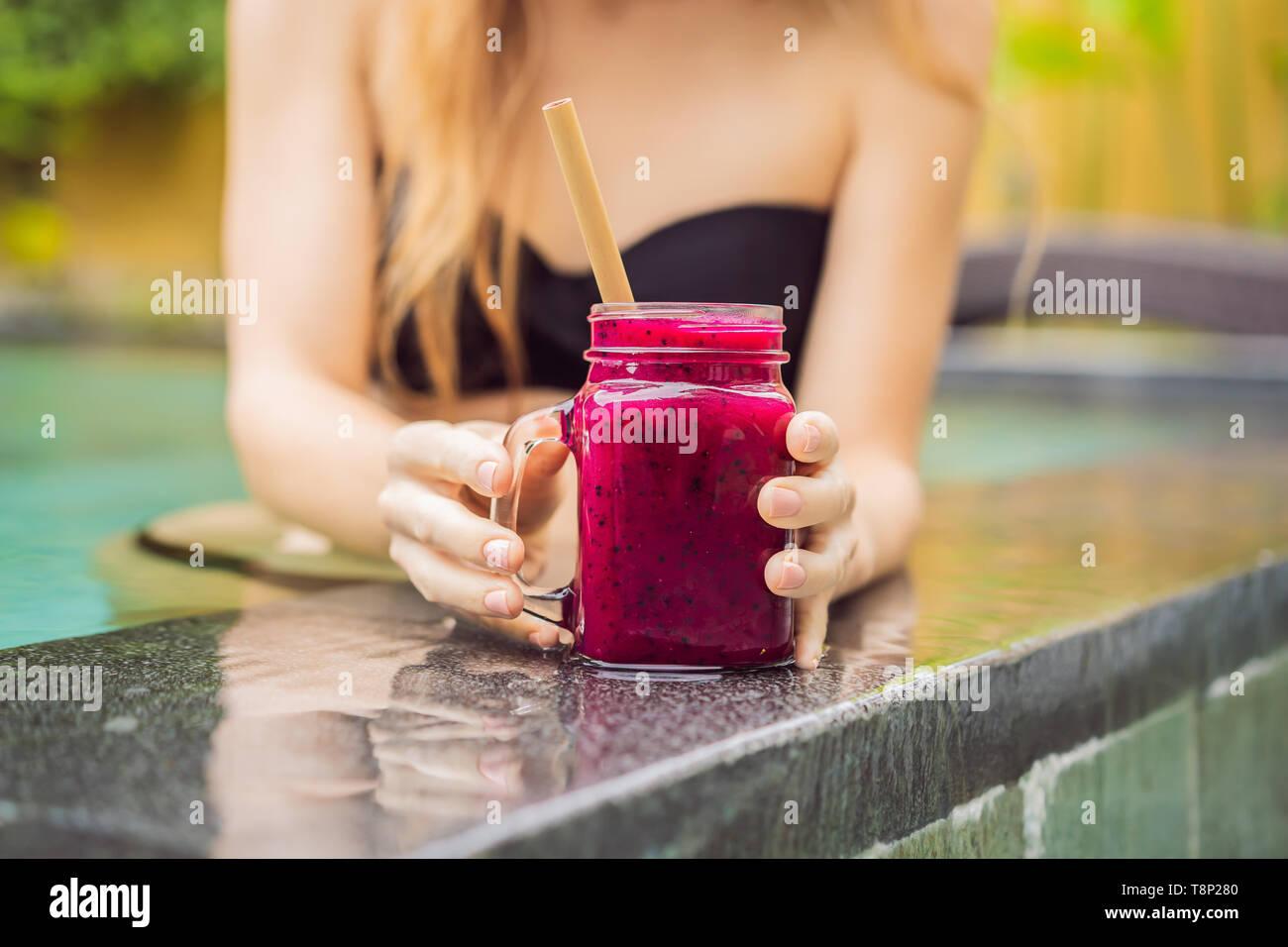 Jeune femme à boire le fruit du dragon, des smoothies sur le fond de la piscine. Smoothie aux fruits - manger sain concept. Close up de smoothie détox avec Banque D'Images