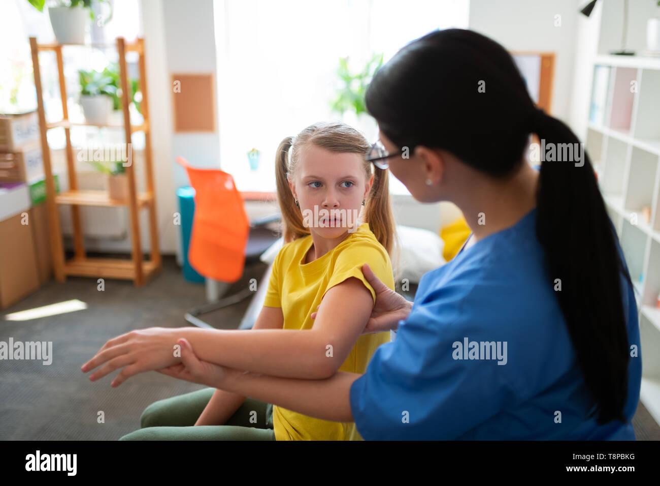Peur blonde girl in yellow t-shirt assis dans le cabinet médical Banque D'Images