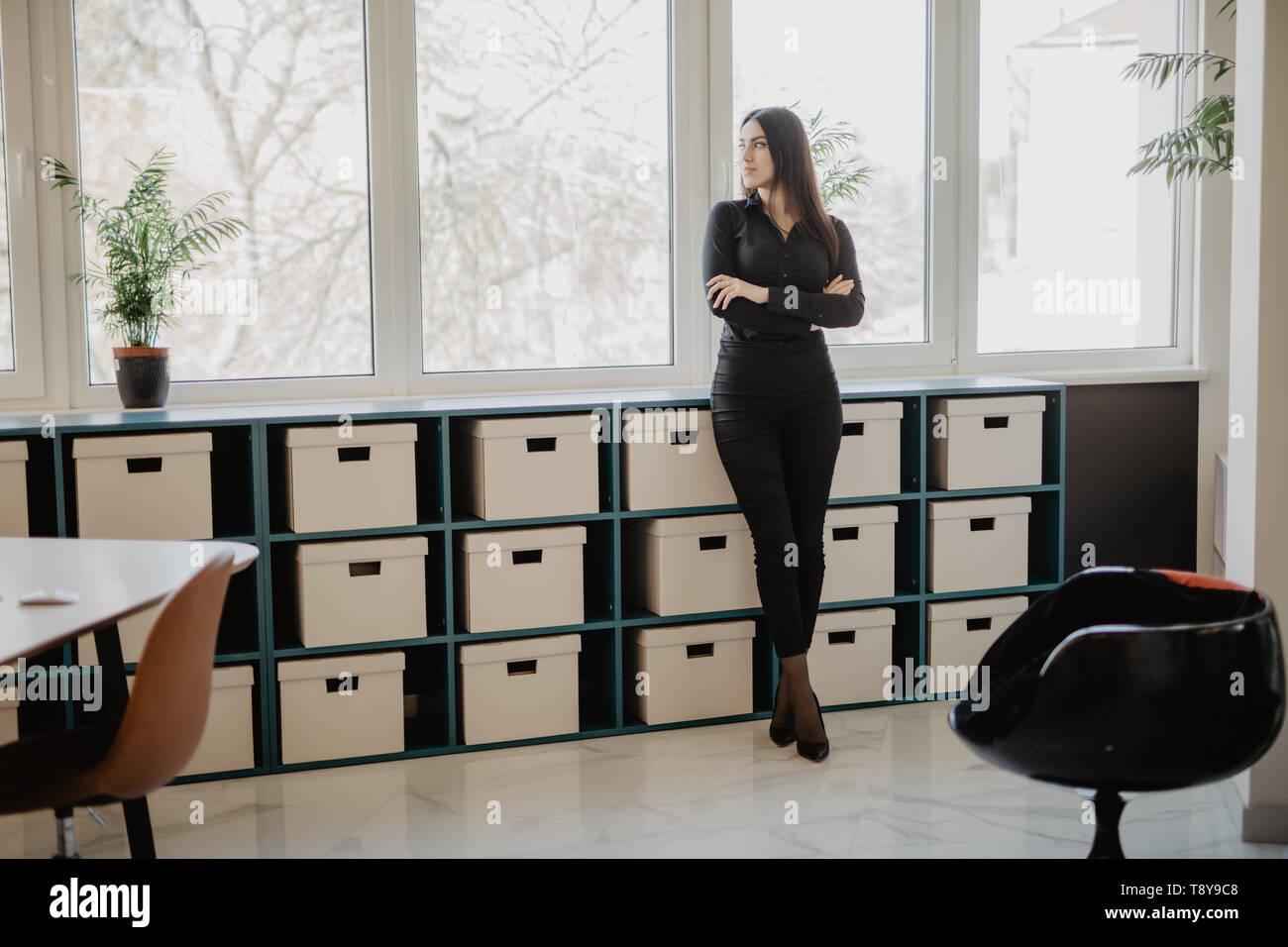 Smiling business woman standing with folded arms in office. Femme en tenue d'affaires formel debout devant son bureau en bureau. Banque D'Images