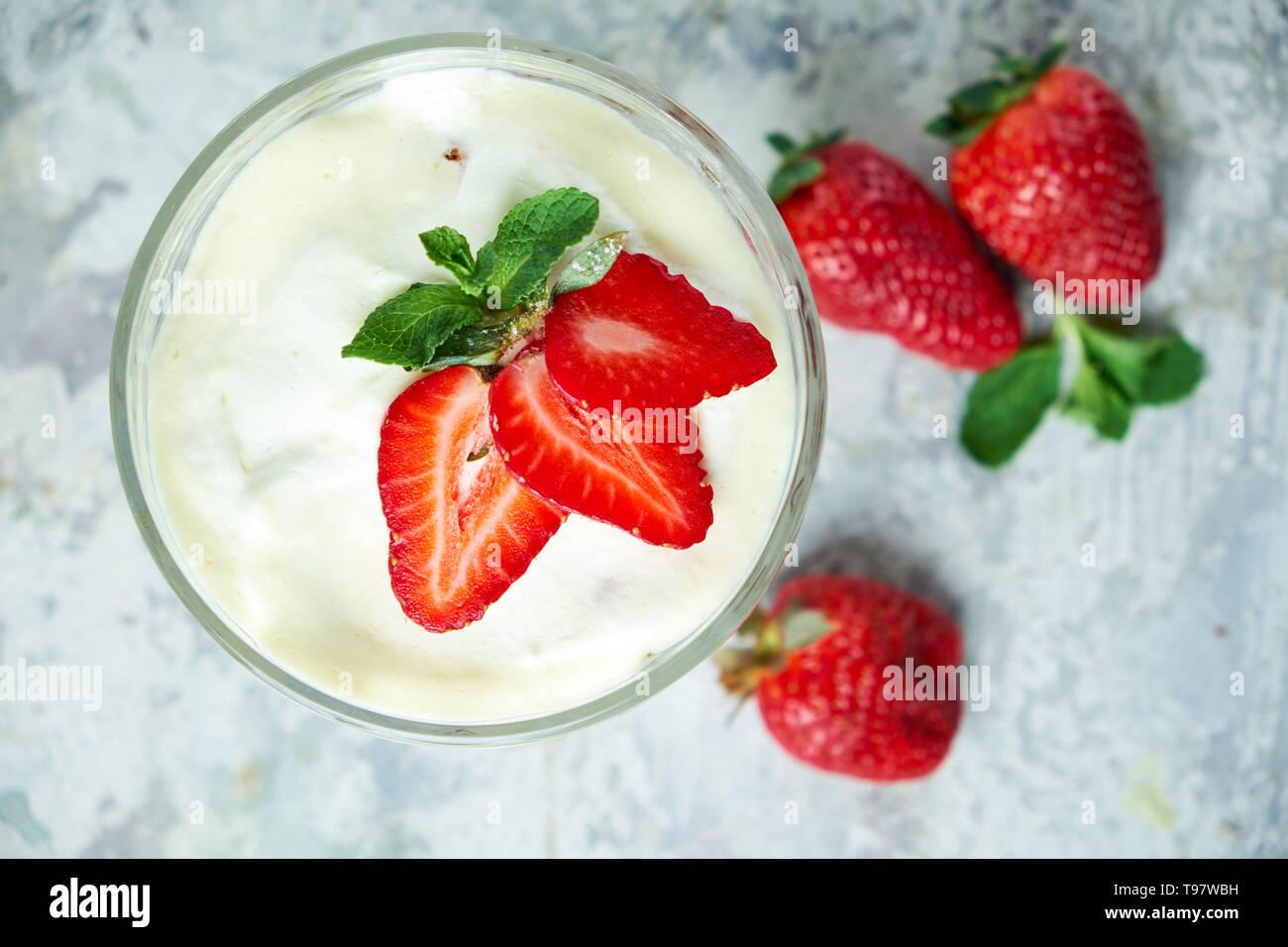 La crème glacée avec des fraises dans un vase de verre. Fond texturé gris. Le Dessert. Vue d'en haut. La chaîne alimentaire Banque D'Images