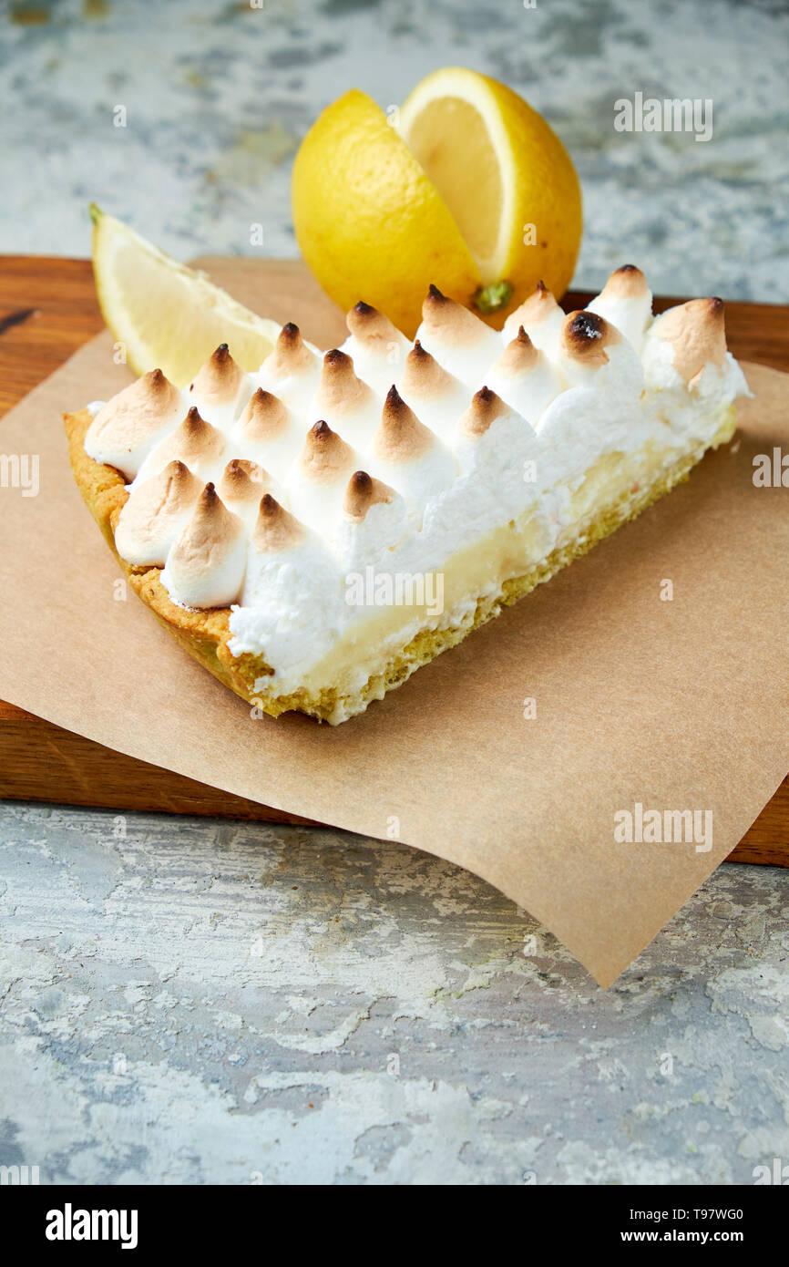 Un morceau de tarte au citron décoré avec une rondelle de citron sur une planche de bois. Fond texturé gris. Beaux plats de service. Le Dessert. La chaîne alimentaire Banque D'Images