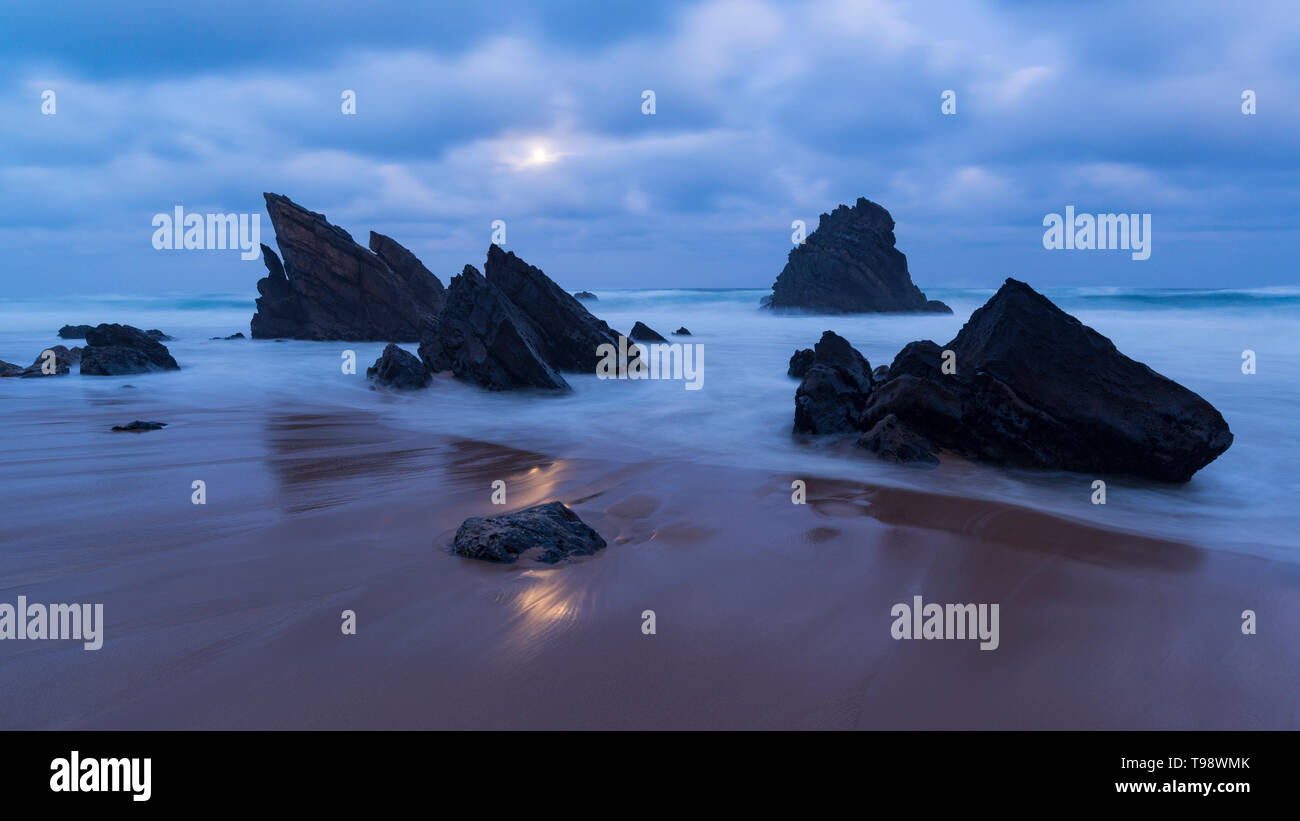Clair de lune sur une plage de sable avec des formations rocheuses, Praia da Adraga, Sintra, Portugal Banque D'Images