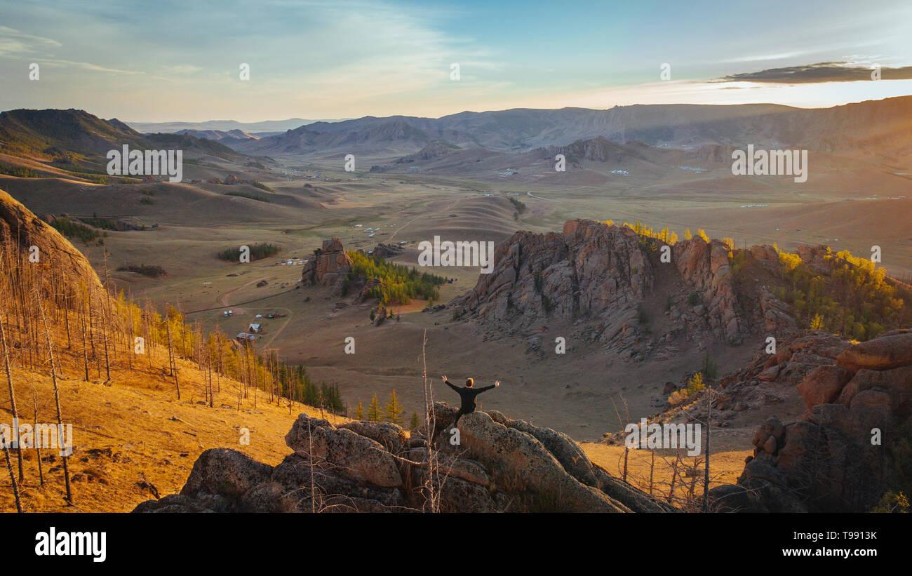 Homme assis sur des rochers avec les bras tendus, le mongol Suisse, désert de Gobi, Mongolie Banque D'Images