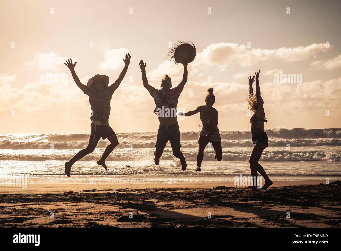 Coucher du soleil à la plage avec des professionnels Groupe de jeunes s'amusant - Saut d'amis sur des vacances locations de profiter ensemble dans l'amitié - Sandy l Banque D'Images