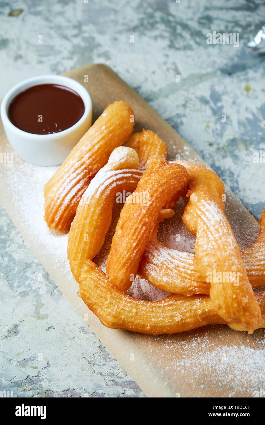 Churos dessert espagnol décoré de sucre glace sur une planche de bois. Fond texturé gris. Beaux plats de service. Le Dessert. La chaîne alimentaire Banque D'Images