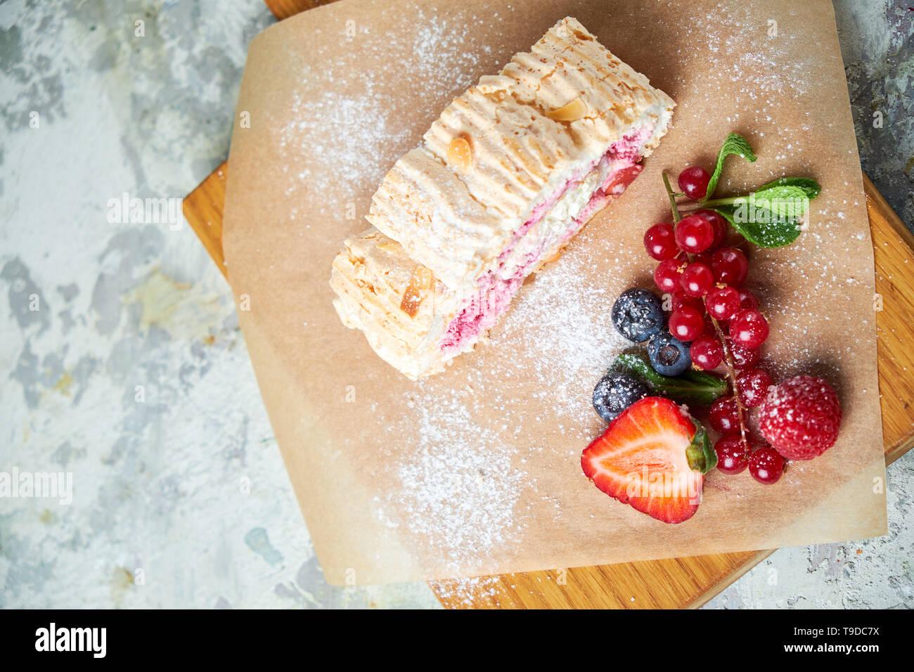 Rouleau de meringue est décoré avec des baies sur une planche de bois. Fond texturé gris. Beaux plats de service. Le Dessert. La chaîne alimentaire Banque D'Images