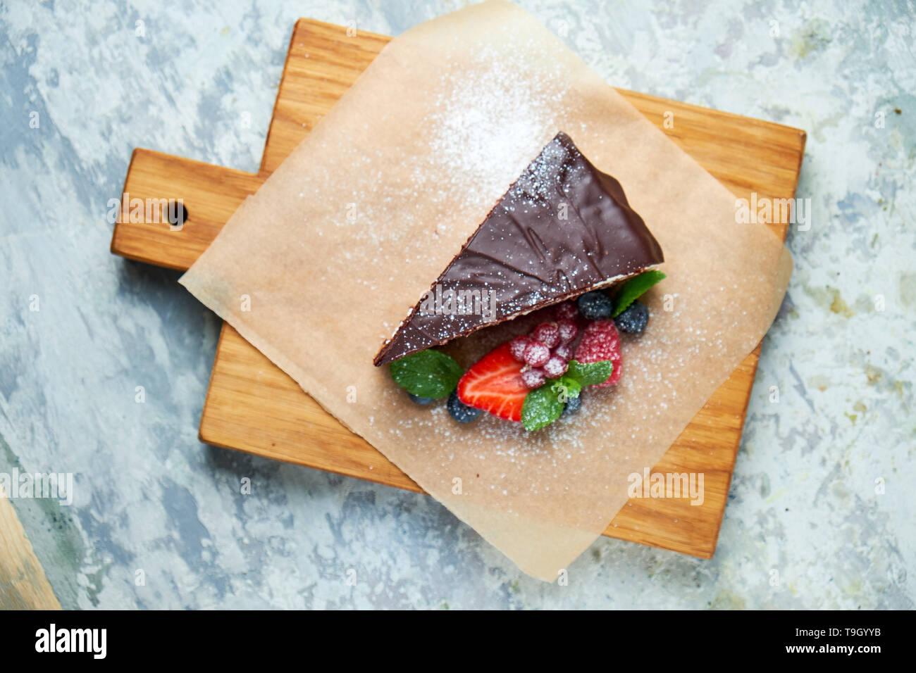 Une tranche de gâteau au chocolat décoré de petits fruits sur une planche de bois. Fond texturé gris. Beaux plats de service. Le Dessert. La chaîne alimentaire Banque D'Images