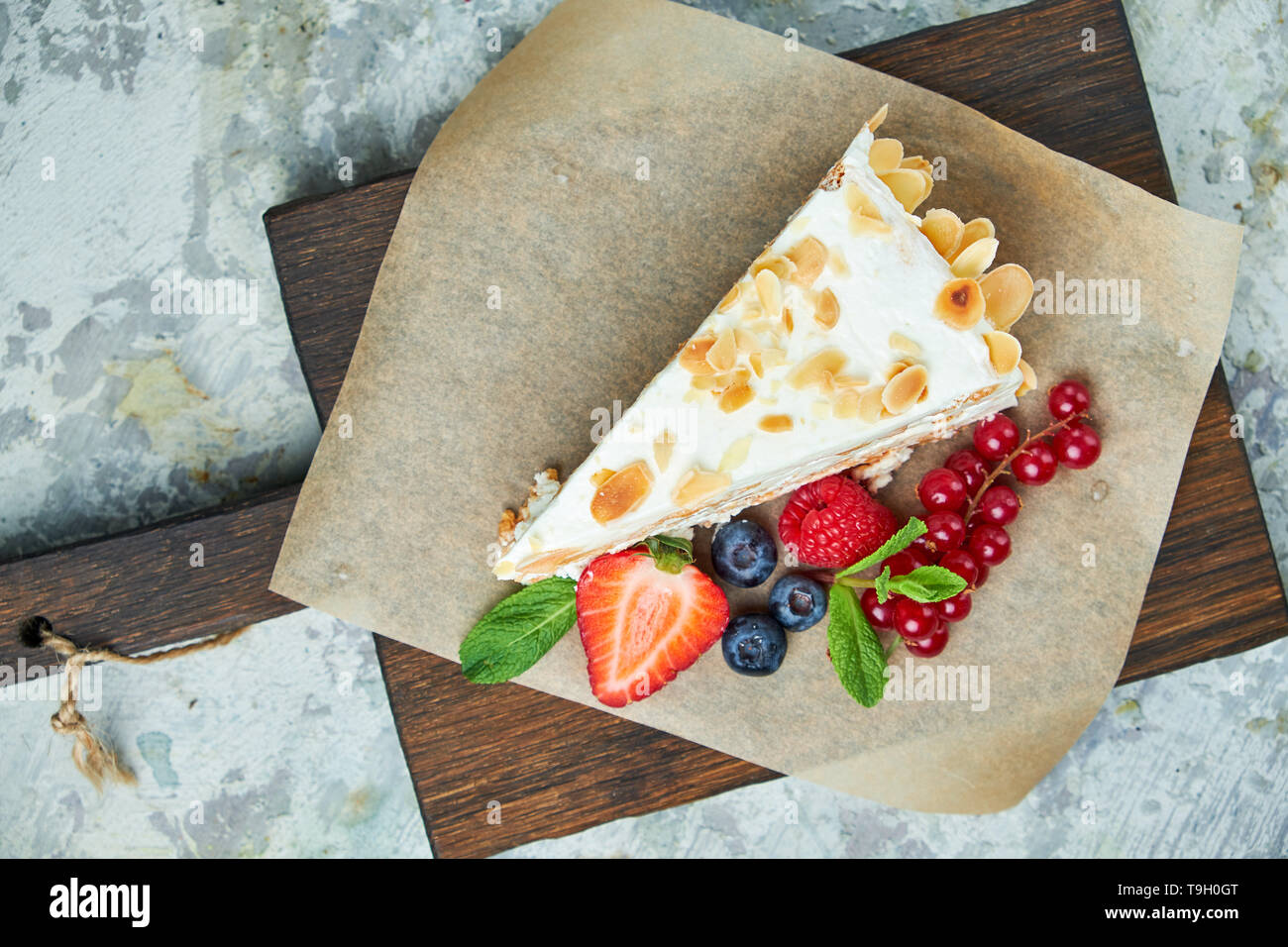 Gâteau meringué aux fraises avec pétales d'amandes, sur fond gris et de journaux Banque D'Images