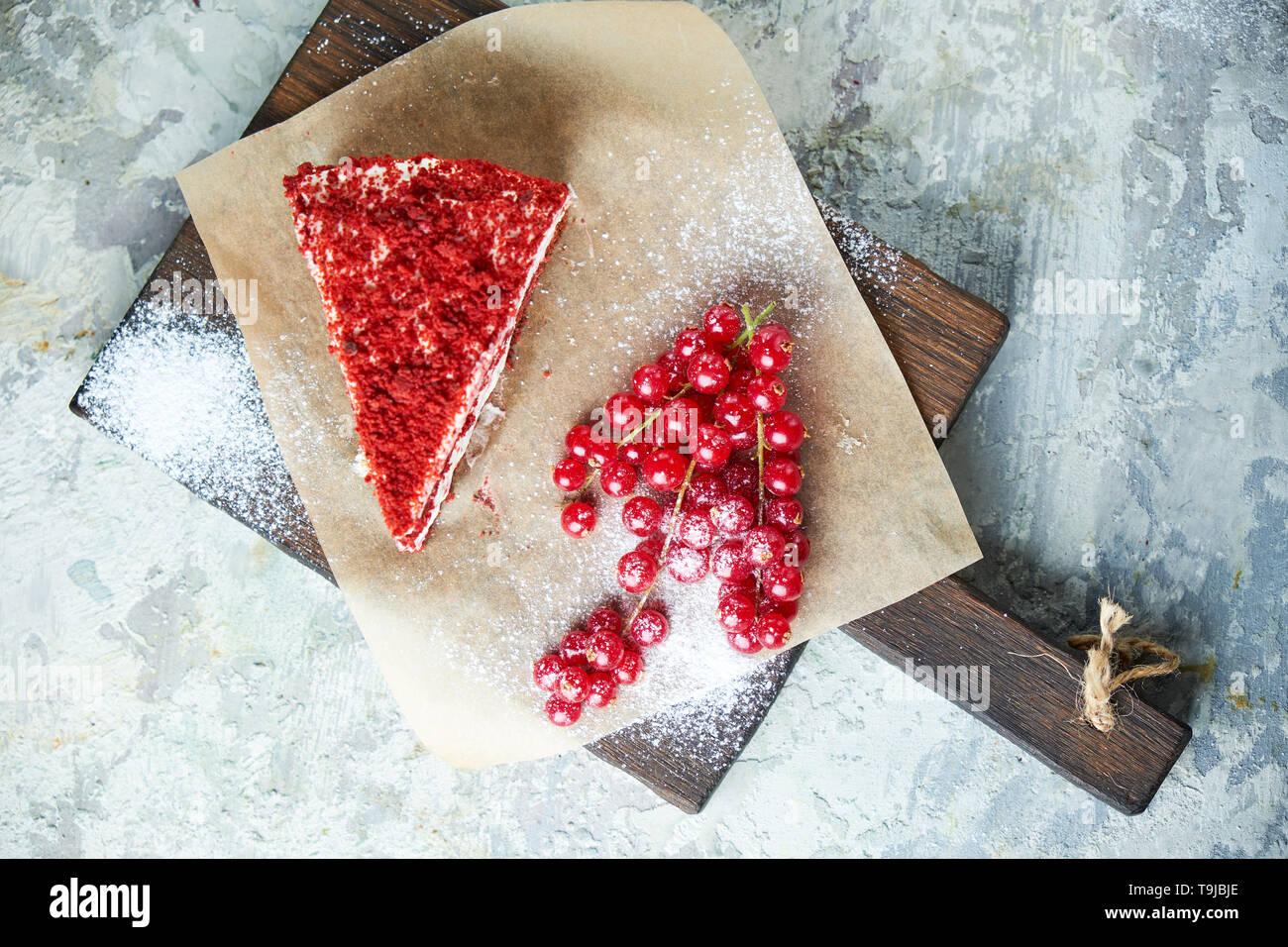 Gâteau de velours rouge et un tas de groseilles rouges sur une planche de bois. Fond texturé gris. Le Dessert. Vue d'en haut. La chaîne alimentaire Banque D'Images